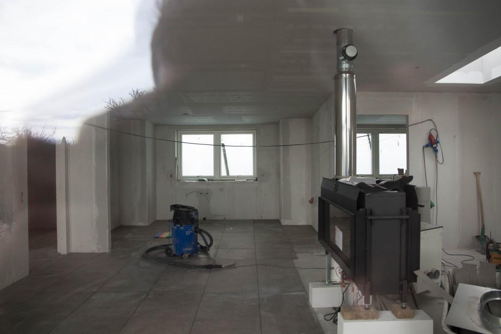Et vindueskig ind, hvor klinkerne er lagt i køkken og køkkenalrum og pejsen med udtræk op på taget.